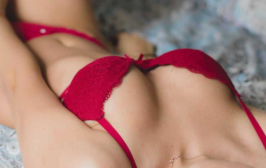 Girl in a red push up bra lying down on a bed