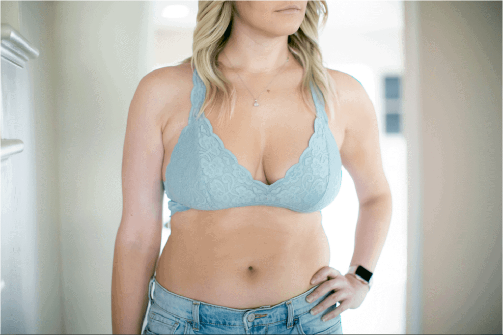 Blonde haired woman wearing a blue lacy bralette and some jean shorts