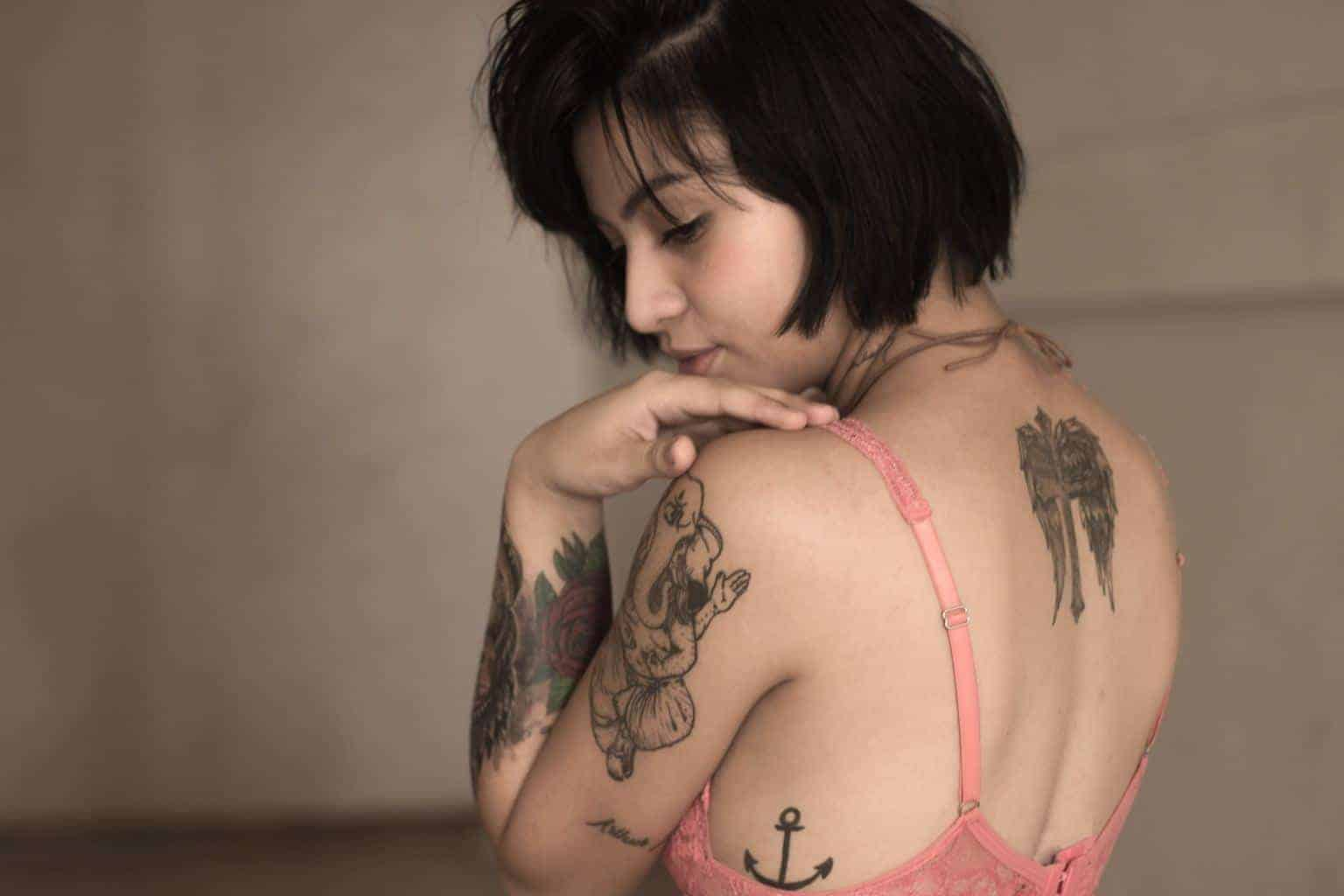 Dark haired woman in a pink bra looks over her shoulder