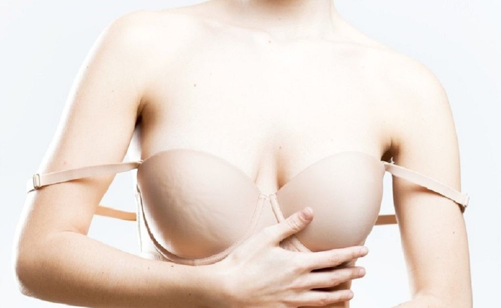 Girl in a nude bra has straps on her elbows from being too long