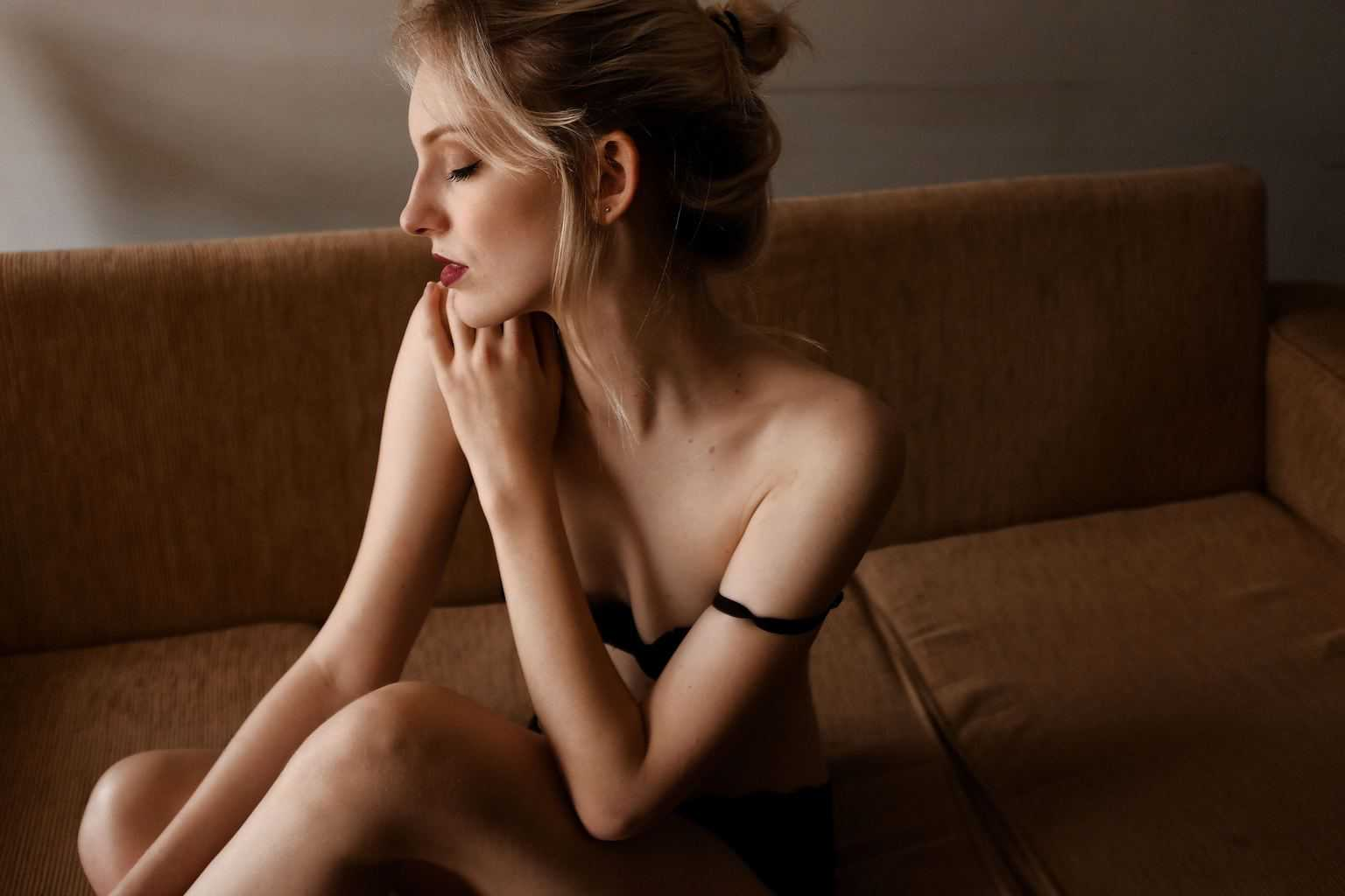 Thin woman sits on a couch while her black bra strap is falling on her arm