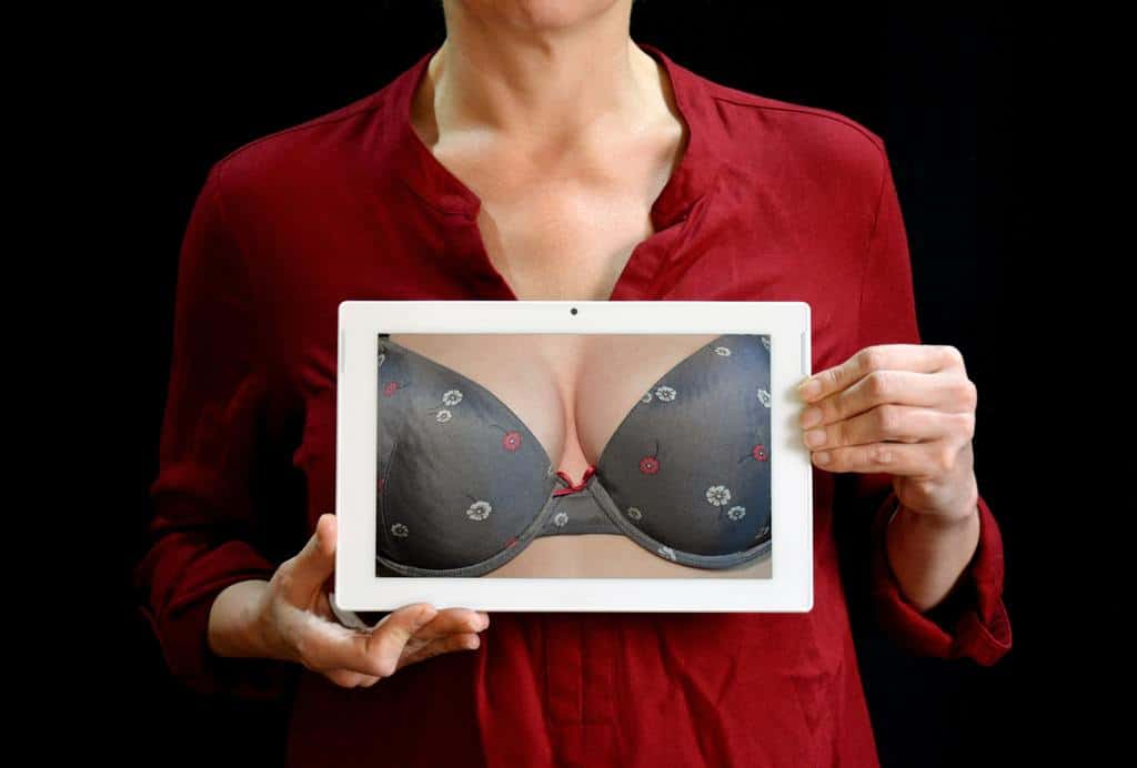 Lady in a red long sleeved top holds a picture to her chest of a bra and breasts