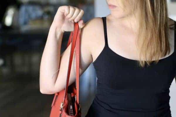 A woman sports a black tank top that hides her black bra strap really well