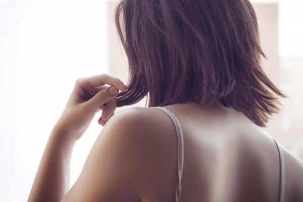 Close up shot of a dark haired girl with shoulder length hair wearing a bra that has a twisted strap