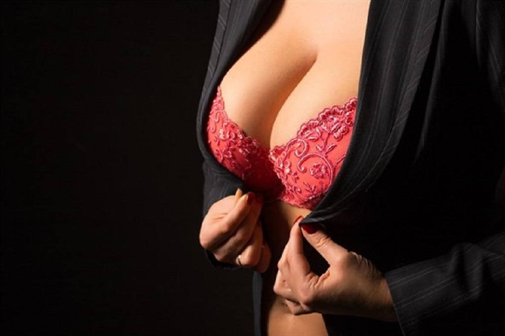 Woman tries to close off her black top while wearing a red lacey bra underneath