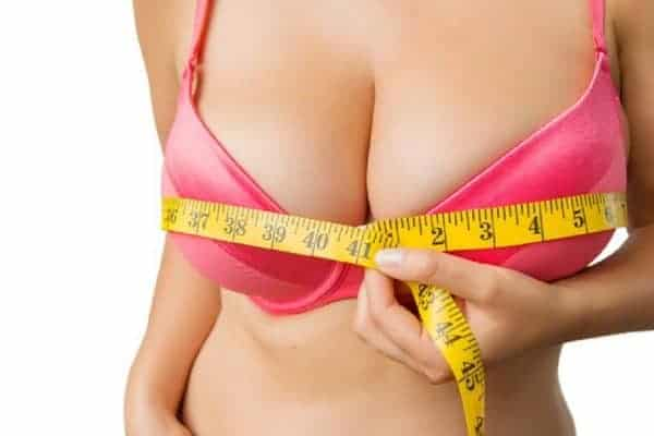 Woman holds a measuring tape arond her boobs as she wears a pink push up bra