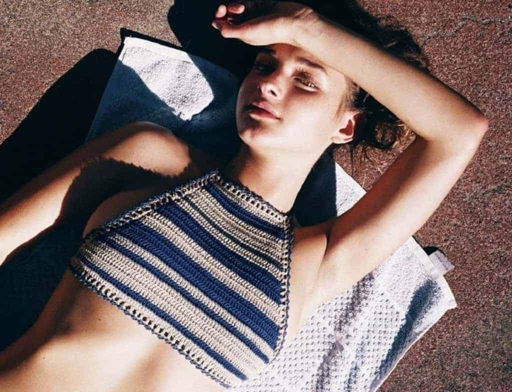 09ac745f0e Girl laying on a towel on the beach wearing a midriff halter top