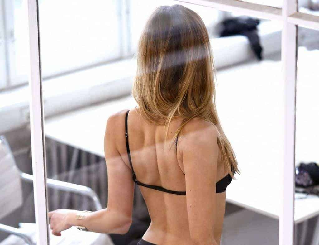 Woman with her back to a glass wall wearing a black bra and black underwear