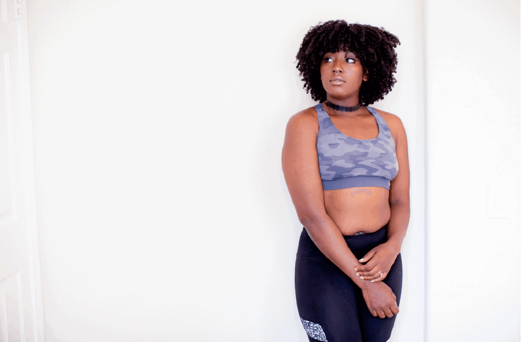Woman in a gray sports bra and gray leggingsis standing infront of a white wall
