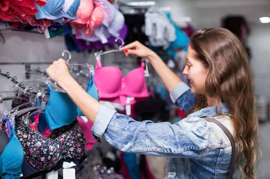 Woman in denim jacket holds up two bras for shopping
