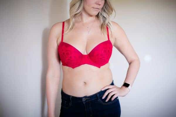 Woman with large sagging breasts wearing a red bra