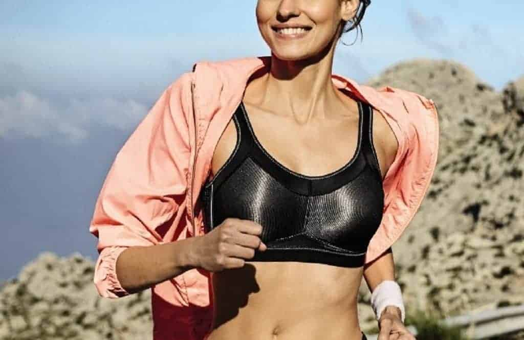 Woman wearing an Anita sports bra running with a pink jacket on