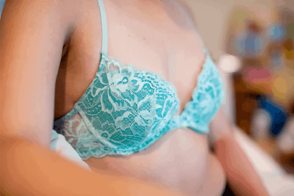 Close up of a woman's chest wearing a blue lace push up bra