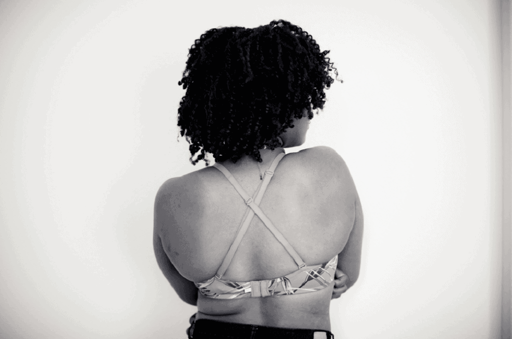 Black and white photo of  woman with her back turned to the camera showing off her racerback bra straps