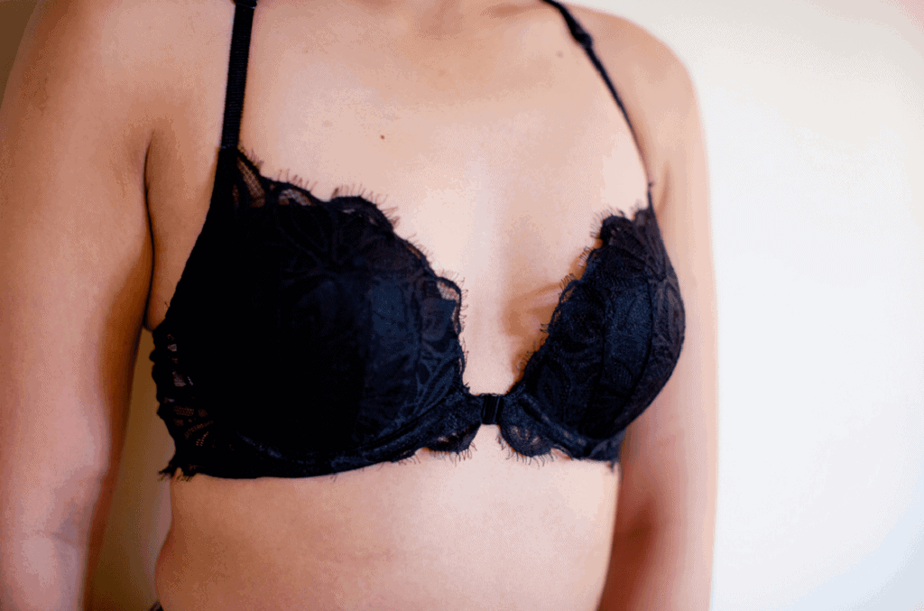 Close up of a woman's chest wearing a lacey black bra