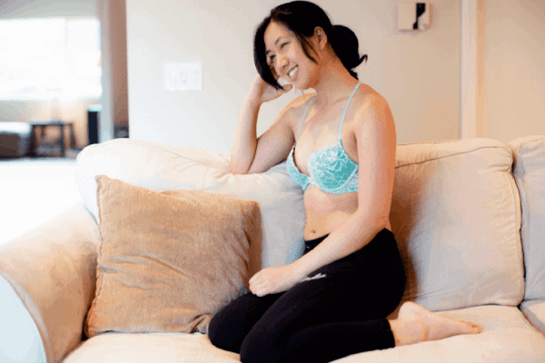 Woman in a blue bra and black pants sits on a couch while giggling