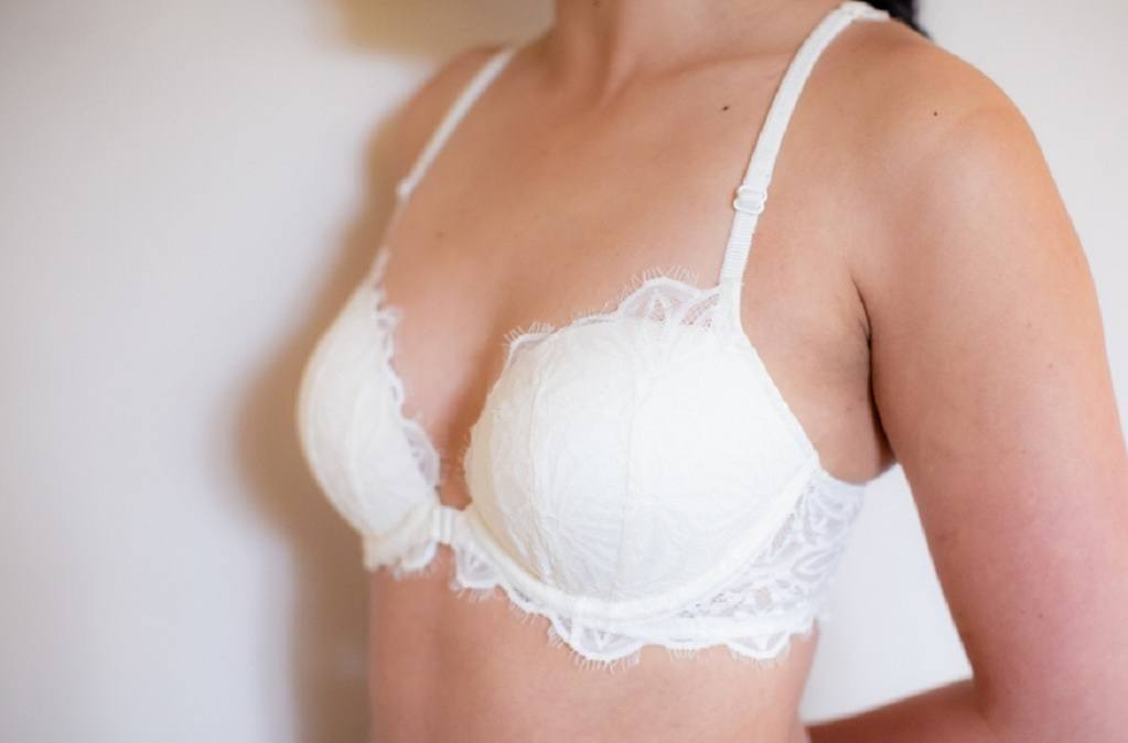 Woman close up wearing a white lacey bra