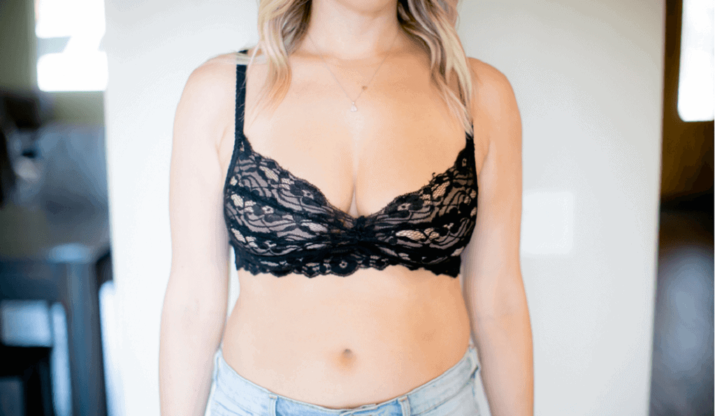 Woman wears a black lacey bralette and light wash jeans