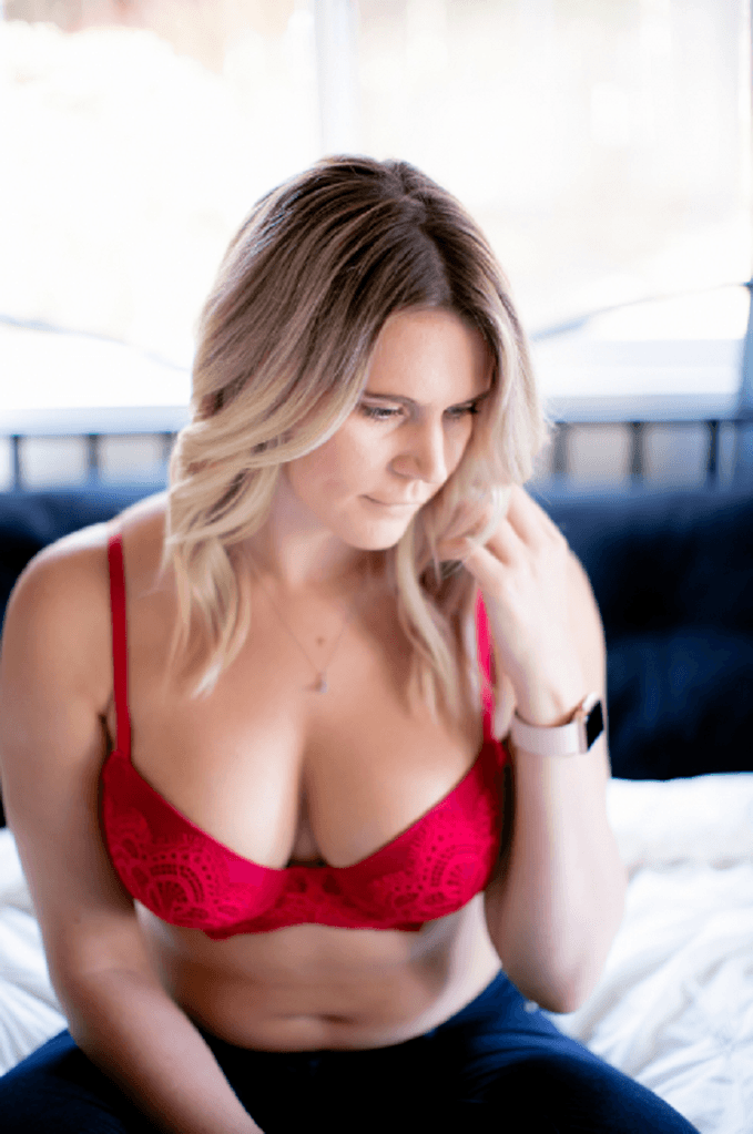 Woman in a red bra sitting on a bed