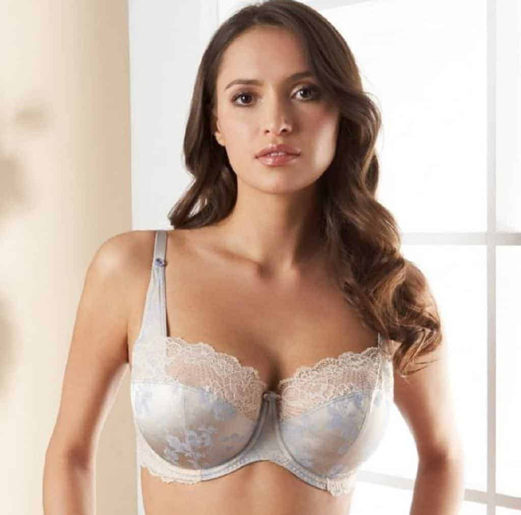 Woman stands in a room wearing a white lacey push up bra