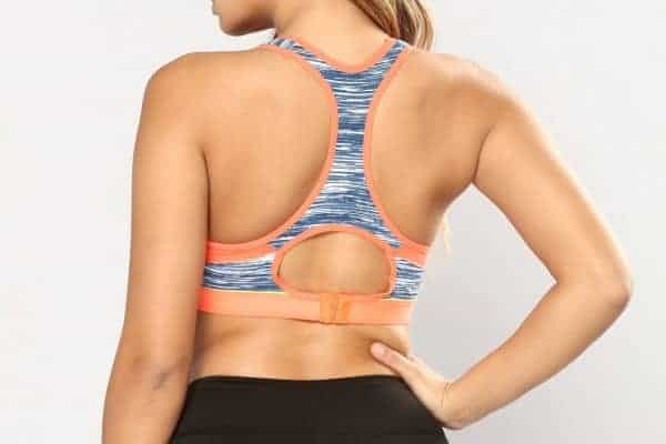 Woman stands with her back to the camera wearing a colorful sports bra and black leggings