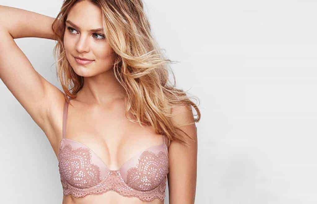 Woman in a lacey pink bra has her hand on her head