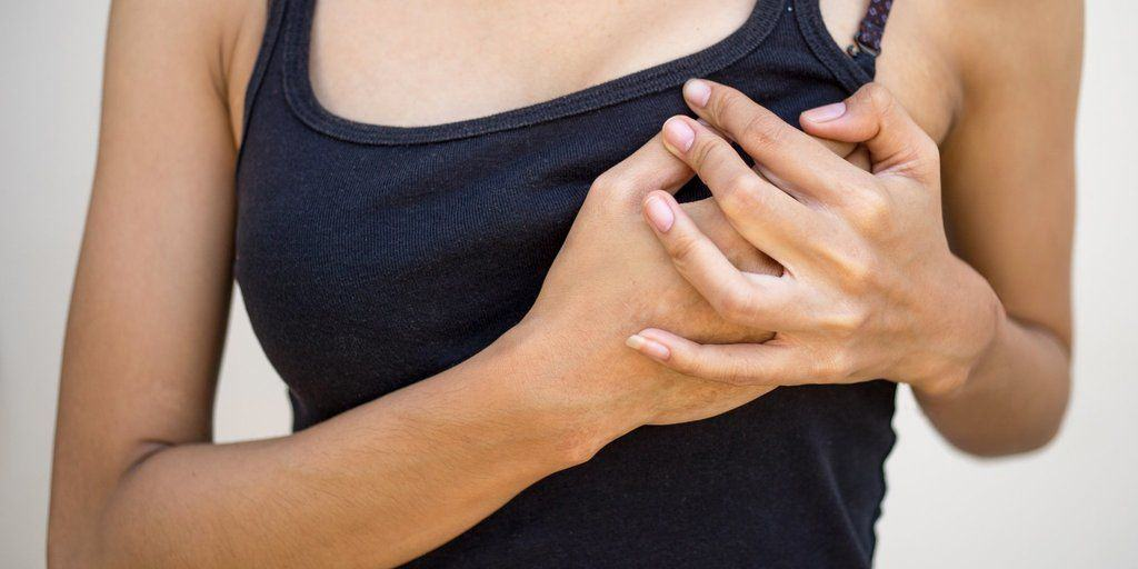 Woman holds her hands to her chest