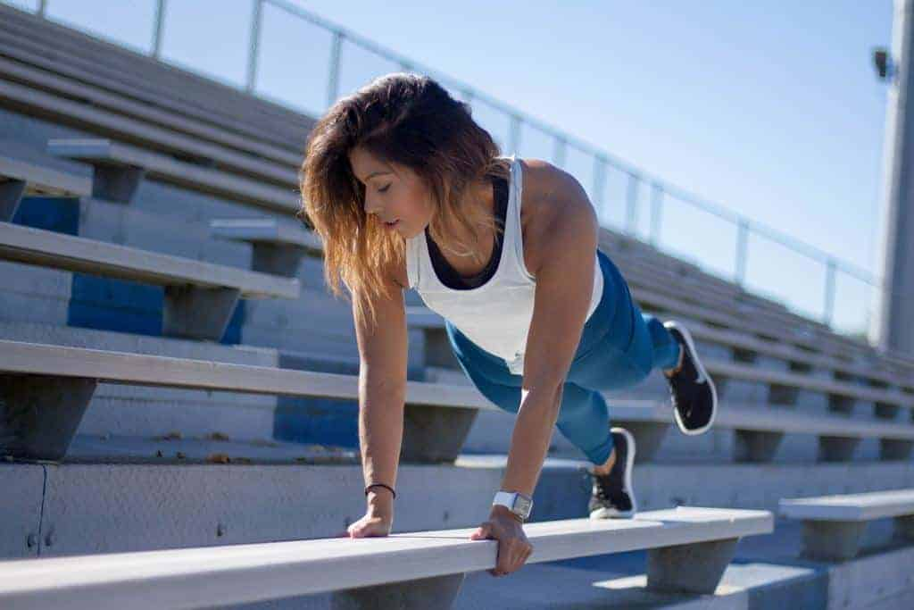 Woman in a white top works out on a grandstand bench