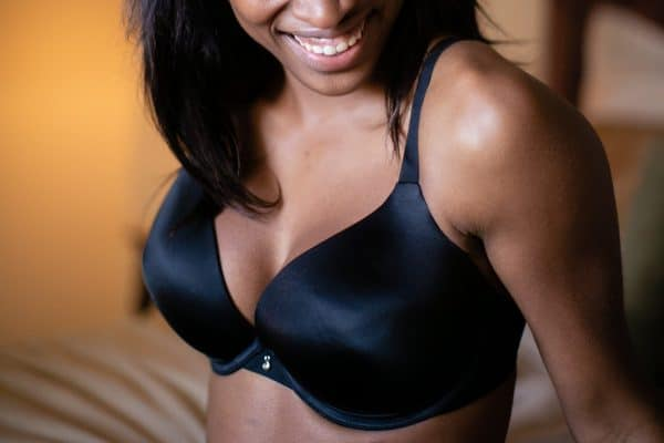 A woman with D cup breasts wears a black pushup bra