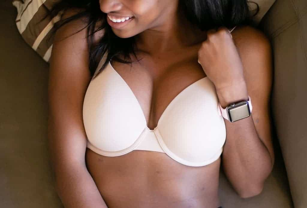 A beautiufl women lies down wearing a bra that provides her breasts with better shape and increased lift.