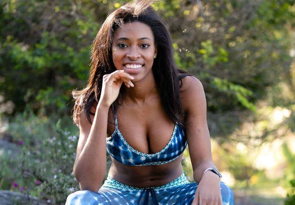 A beautiful black woman with a big bust sits in a sports bra and workout leggings