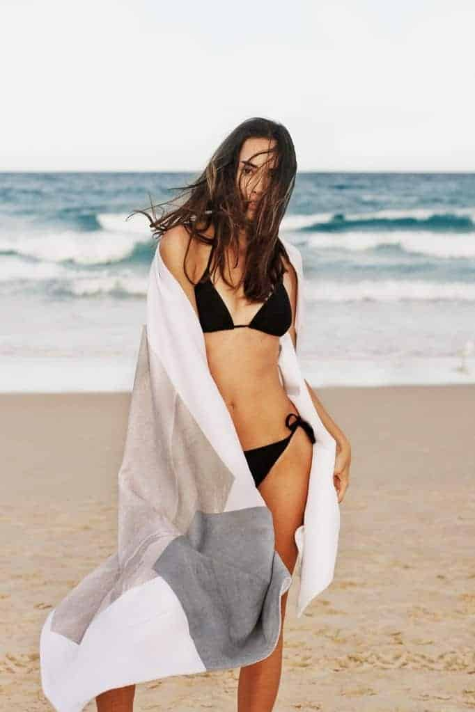 Woman in a black swimsuit and a white cover-up