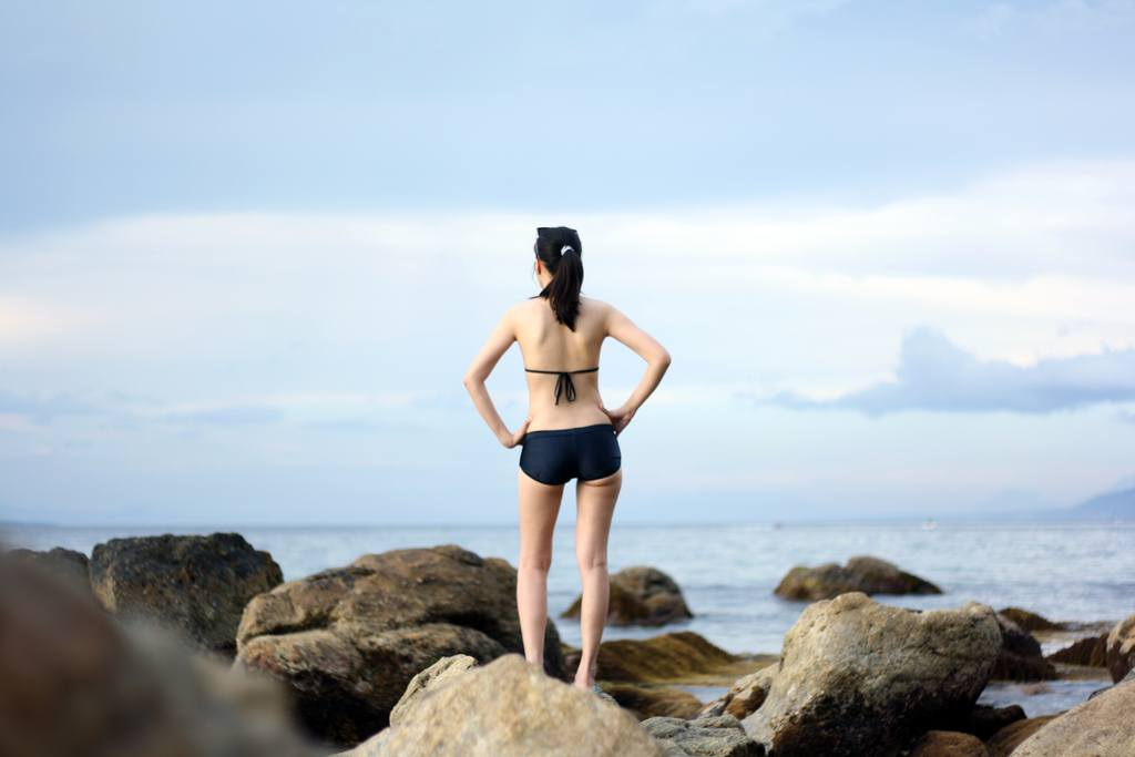 Woman standing on the rocks in a black bikini