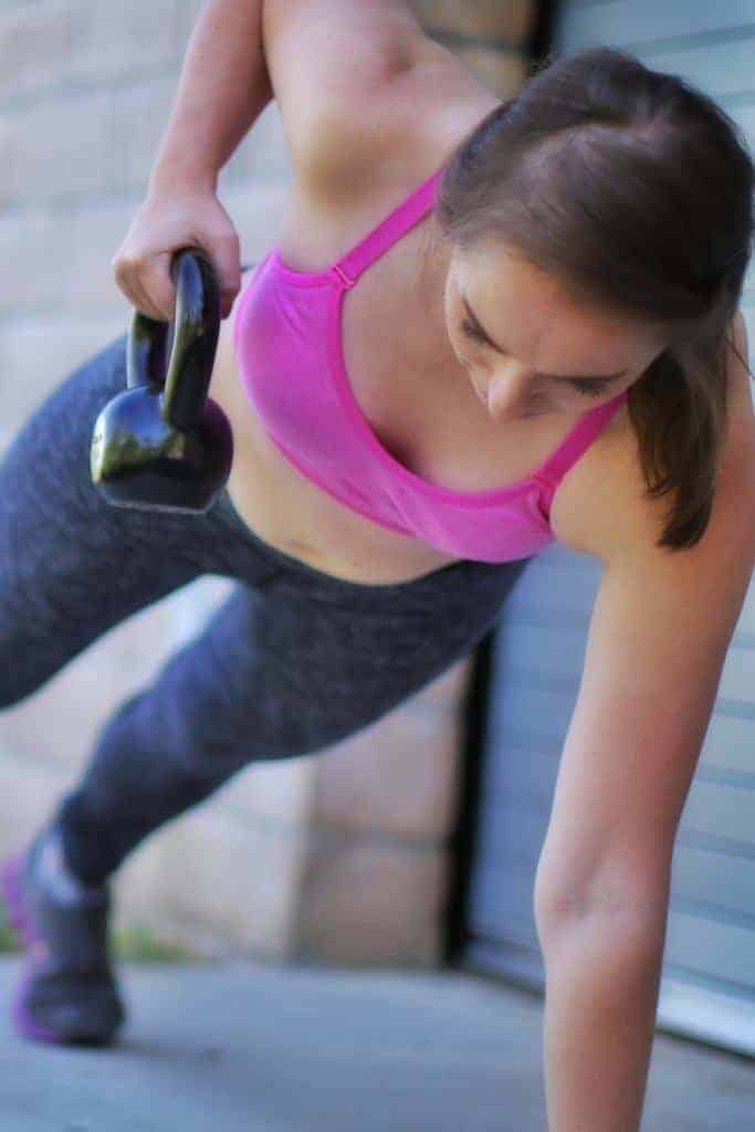 A young woman lifts a kettlebell to get her body in shape for a bikini