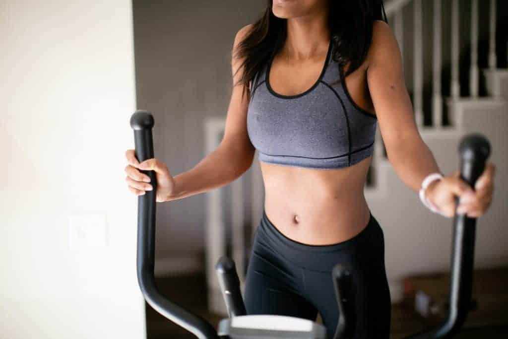 Woman using a Stairmaster while wearing a gray sports bra and black leggings