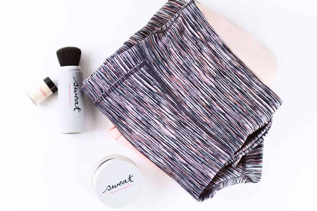 Folded gray nad pink leggings on top of a white background