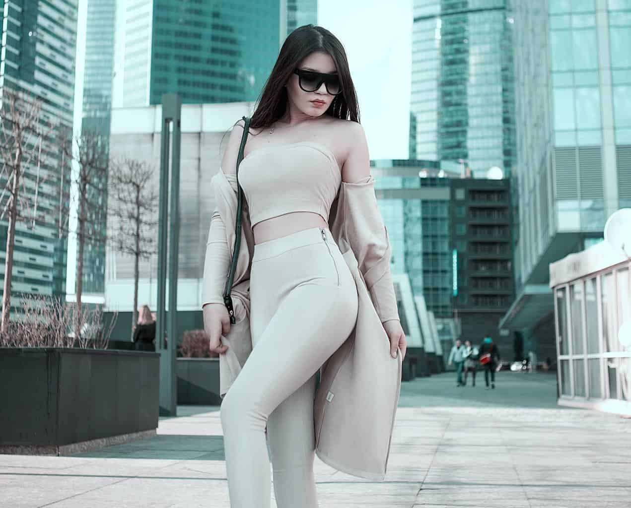 Woman in a nude tube top and leggings with a matching coat and sunglasses