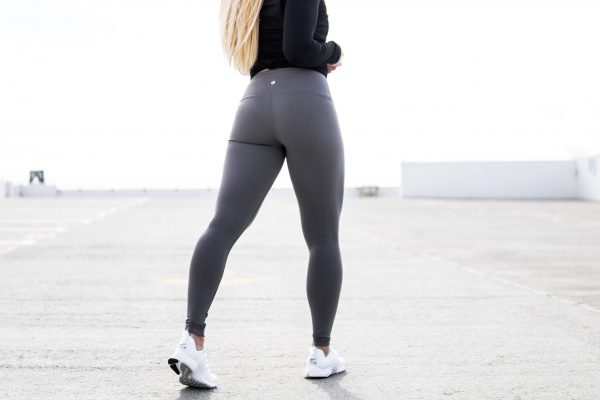 Close up of woman wearing gray yoga pants and a black long sleeved top