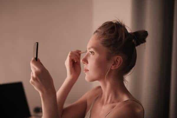 Woman in a bun applies make up to her face