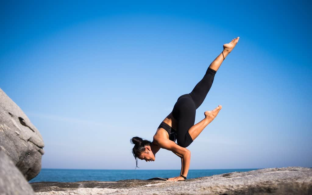 Woman in a black sports bra and yoga pants in front of a shore doing a yoga position