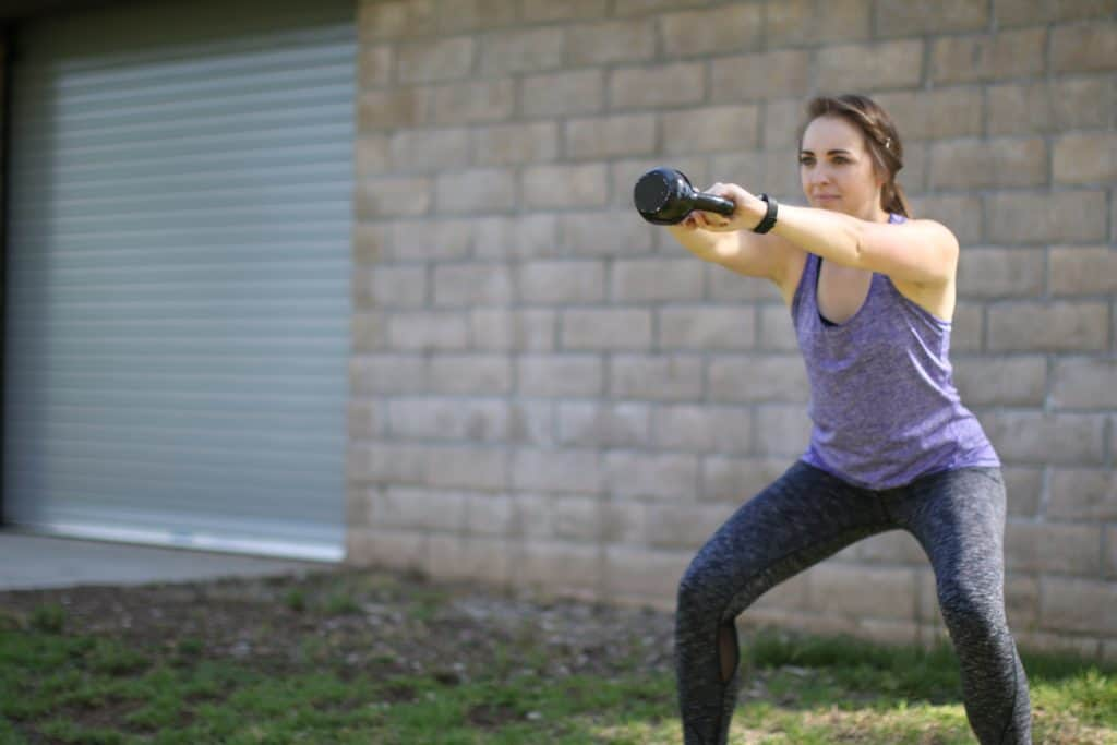 A woman uses a kettlebell to exercise and work out