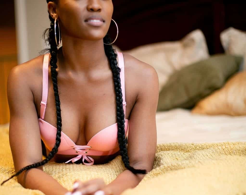 Woman on the bed in a pink push up bra and braids