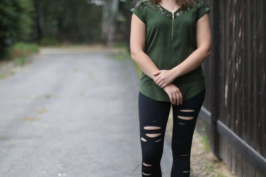 Woman in a green shirt and ripped jeans standing on a road