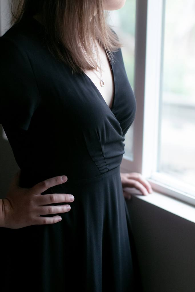 Woman by a window wearing a black deep v dress