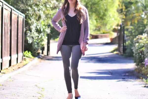 Woman standing in the middle of the road in a top, jacket, and leggings