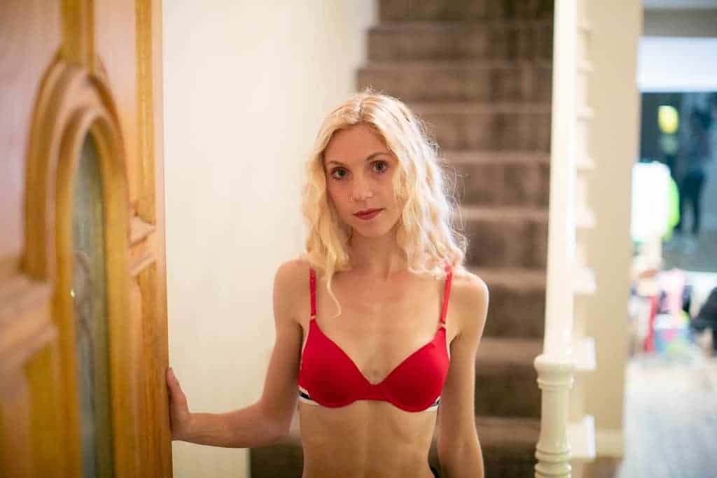 Woman by the doorway wearing a red bra