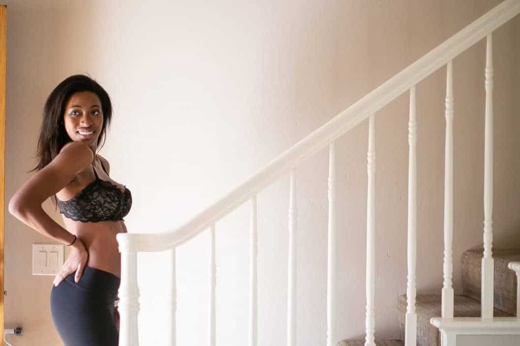 Woman in a lacey black balconette bra in front of a white stair case