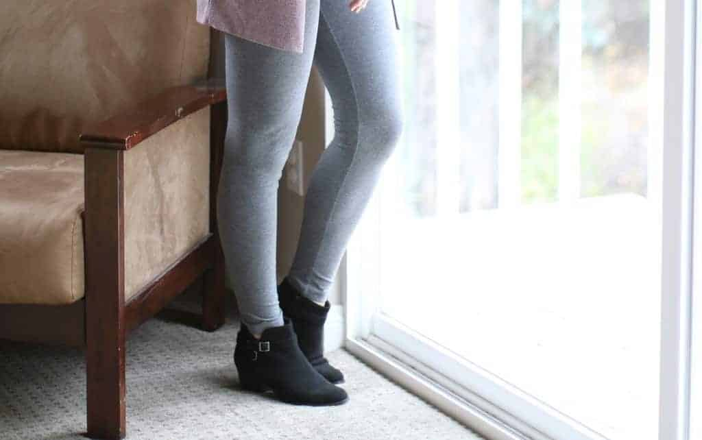 Woman in gray leggings wearing ankle boots
