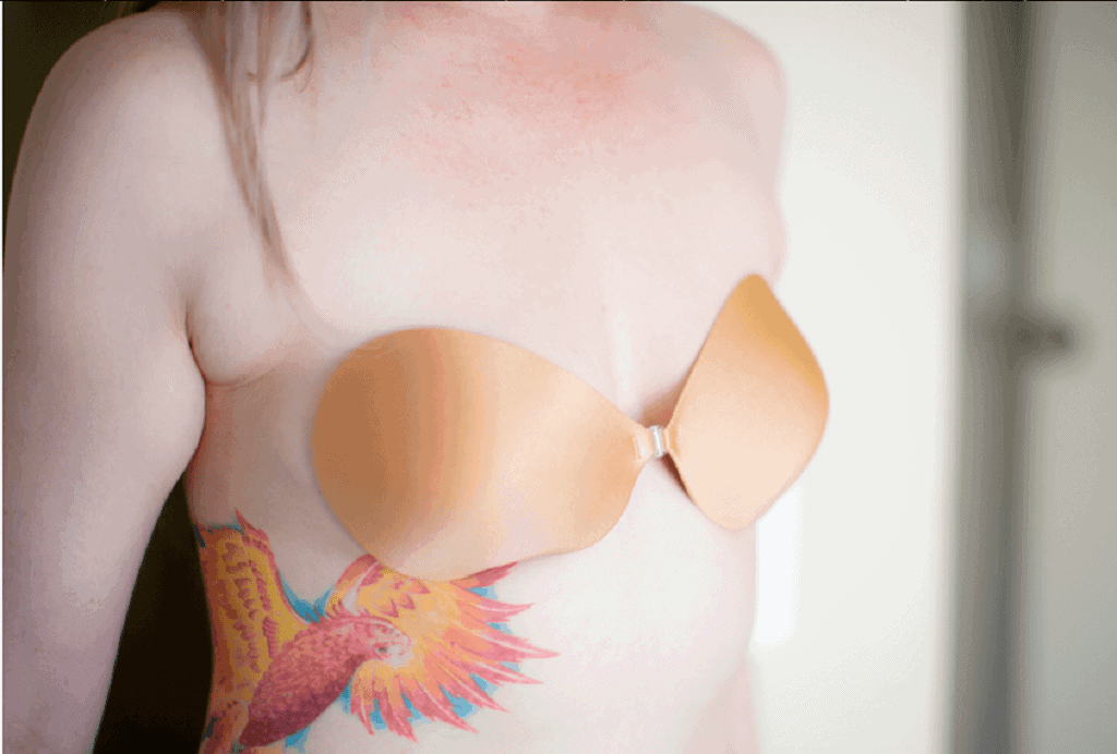 Woman with a tattoo on her chest wears a nude adhesive bra