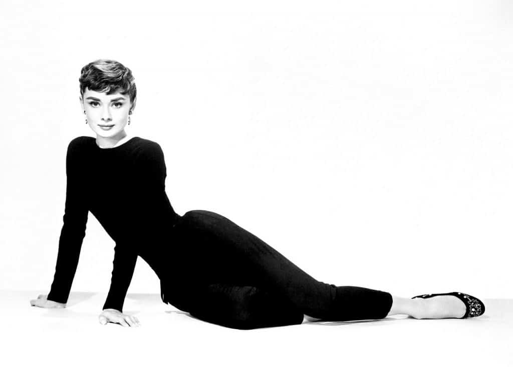 Audrey Hepburn posing on a white backdrop wearing a black top and black leggings